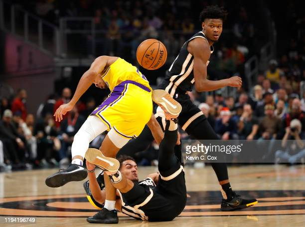 Trae Young of the Atlanta Hawks battles for a loose ball against Avery Bradley of the Los Angeles Lakers in the first half at State Farm Arena on...