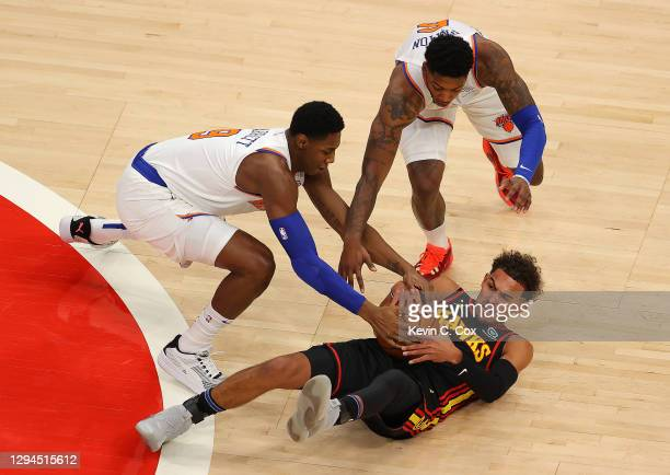Trae Young of the Atlanta Hawks battles for a loose ball against RJ Barrett and Elfrid Payton of the New York Knicks during the first half at State...