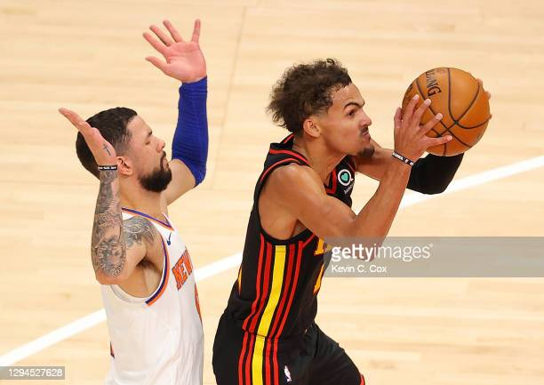 Trae Young of the Atlanta Hawks draws a foul from Austin Rivers of the New York Knicks during the second half at State Farm Arena on January 04, 2021...