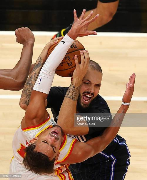 Trae Young of the Atlanta Hawks draws an offensive foul from Evan Fournier of the Orlando Magic during a preseason game at State Farm Arena on...