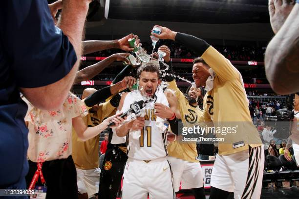 Trae Young of the Atlanta Hawks drenched by teammates after victory over the Philadelphia 76ers on March 23 2019 at State Farm Arena in Atlanta...