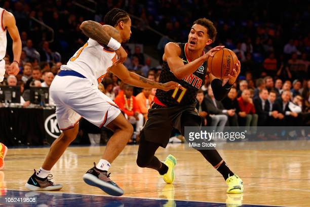 Trae Young of the Atlanta Hawks dribbles the ball against Trey Burke of the New York Knicks at Madison Square Garden on October 17 2018 in New York...