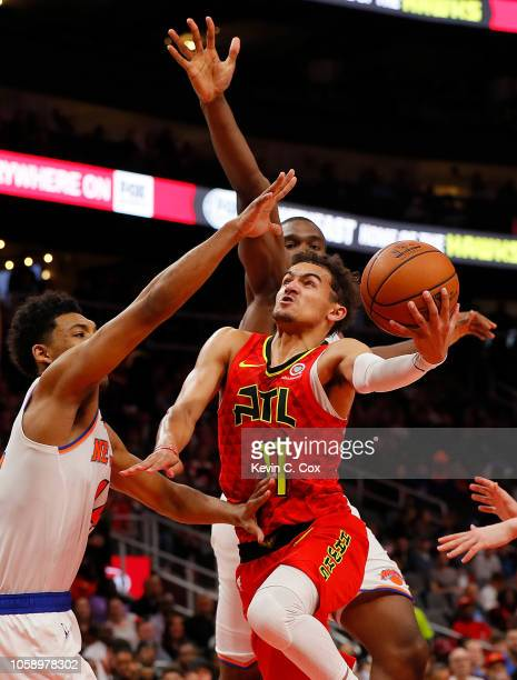 Trae Young of the Atlanta Hawks drives against Noah Vonleh and Allonzo Trier of the New York Knicks at State Farm Arena on November 7 2018 in Atlanta...
