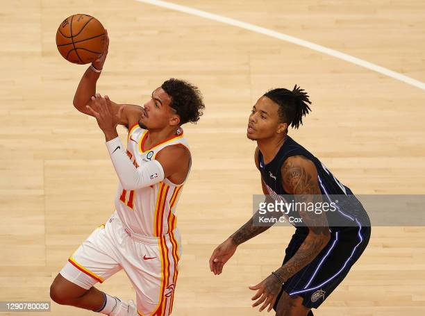 Trae Young of the Atlanta Hawks drives past Markelle Fultz of the Orlando Magic during a preseason game at State Farm Arena on December 11, 2020 in...