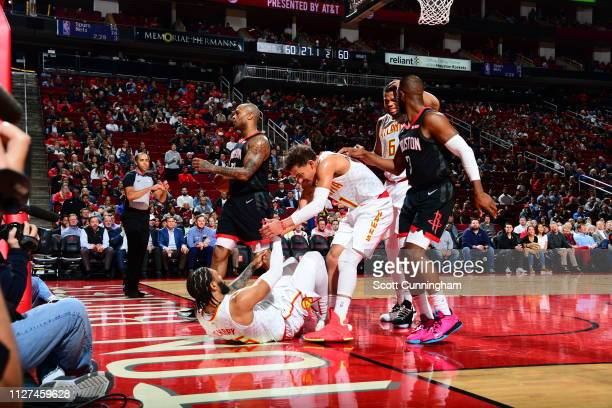 Trae Young of the Atlanta Hawks helps teammate DeAndre' Bembry of the Atlanta Hawks from the floor during the game against the Houston Rockets on...