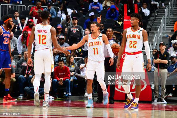 Trae Young of the Atlanta Hawks high fives his teammate during the game against the New York Knicks on March 11, 2020 at State Farm Arena in Atlanta,...