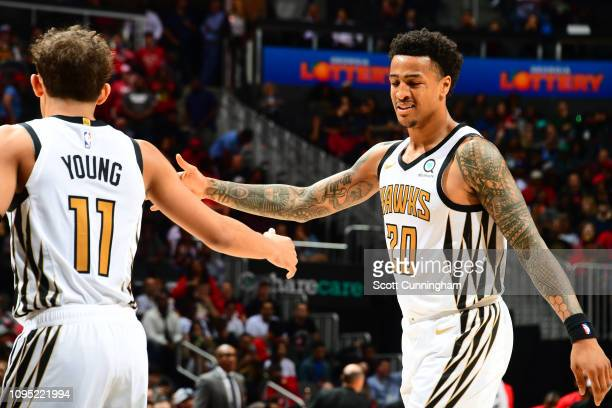Trae Young of the Atlanta Hawks highfives John Collins of the Atlanta Hawks during the game against the Toronto Raptors on February 7 2019 at State...