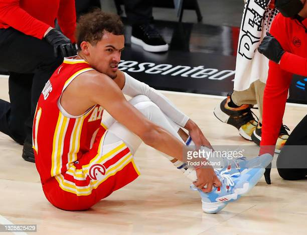 Trae Young of the Atlanta Hawks holds his ankle after an injury during the second half in game three of the Eastern Conference Finals against the...
