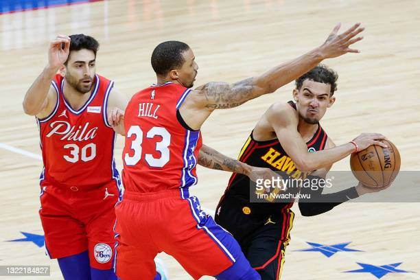 Trae Young of the Atlanta Hawks looks to pass past George Hill of the Philadelphia 76ers during the fourth quarter during Game One of the Eastern...
