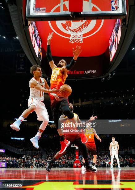 Trae Young of the Atlanta Hawks passes around Rudy Gobert of the Utah Jazz during the second half of an NBA game at State Farm Arena on December 19...