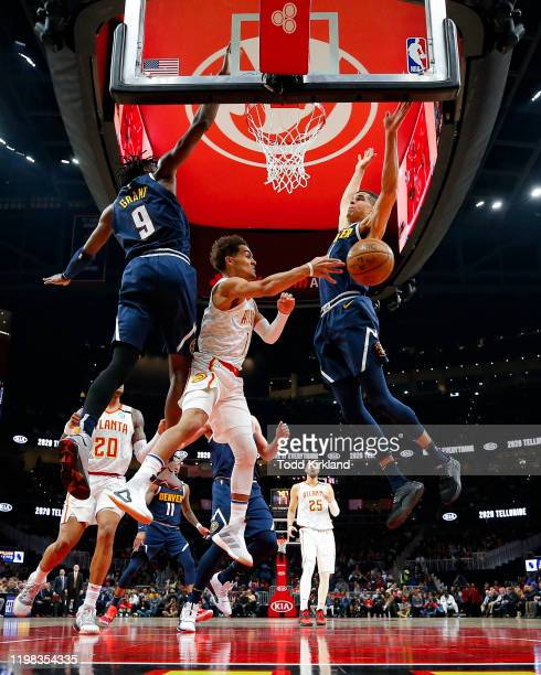 Trae Young of the Atlanta Hawks passes as Jerami Grant and Michael Porter Jr. #1 of the Denver Nuggets defend during the first half of an NBA game at...