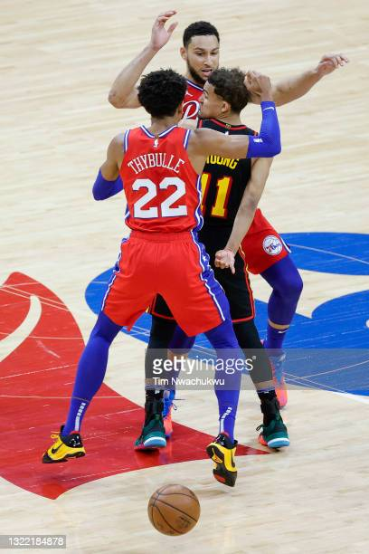Trae Young of the Atlanta Hawks passes between Ben Simmons and Matisse Thybulle of the Philadelphia 76ers during the fourth quarter during Game One...