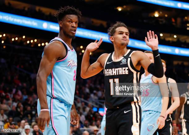 Trae Young of the Atlanta Hawks reacts alongside Jimmy Butler of the Miami Heat during the second half of an NBA game at State Farm Arena on February...