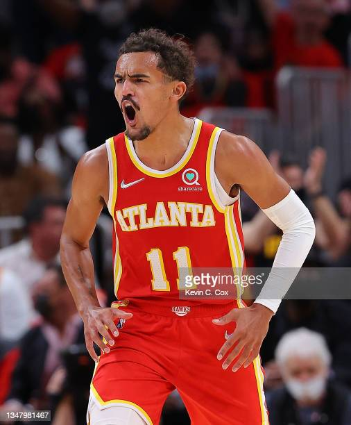 Trae Young of the Atlanta Hawks reacts assisting on a dunk by Clint Capela against the Dallas Mavericks during the first half at State Farm Arena on...