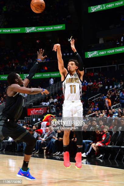 Trae Young of the Atlanta Hawks shoots three point basket over Reggie Jackson of the Detroit Pistons on February 22 2019 at State Farm Arena in...