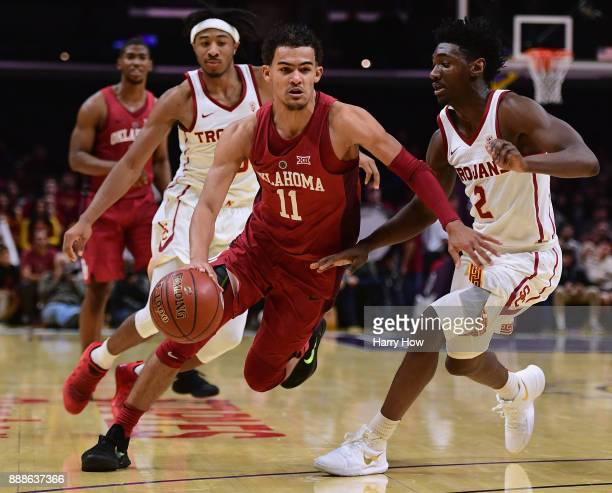 Trae Young of the Oklahoma Sooners drives on Jonah Mathews of the USC Trojans in an 8583 Sooner win during the Basketball Hall of Fame Classic at...