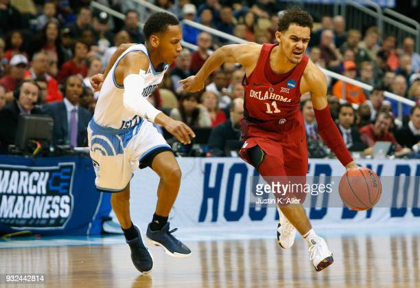 Trae Young of the Oklahoma Sooners is defended by Fatts Russell of the Rhode Island Rams in the first half of the game during the first round of the...