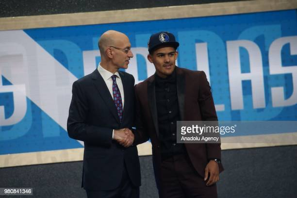 Trae Young shakes hands with NBA Commissioner Adam Silver after being drafted fifth overall by the Dallas Mavericks during the 2018 NBA Draft at...