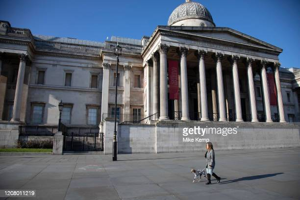 Trafalgar Square and the National Gallery empty and almost deserted apart from a dog walker due to the Covid-19 outbreak social distancing on what...