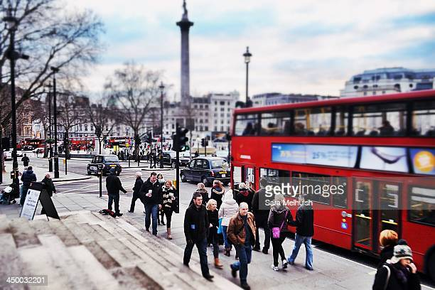 Trafalgar Square, London, during the weekend in the bleak winter with the usual bustle of colorful people walking in the foreground and buses and...