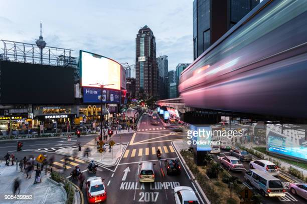 Traffic and a monorail car rush through the Bukit Bintang intersection at night in Kuala Lumpur