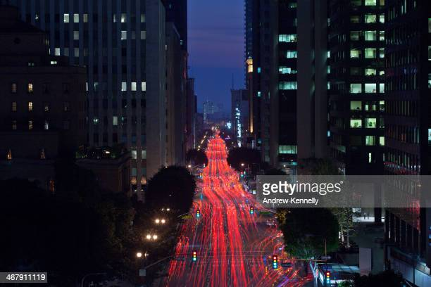 Traffic and lights flow on a busy street in downtown Los Angeles.