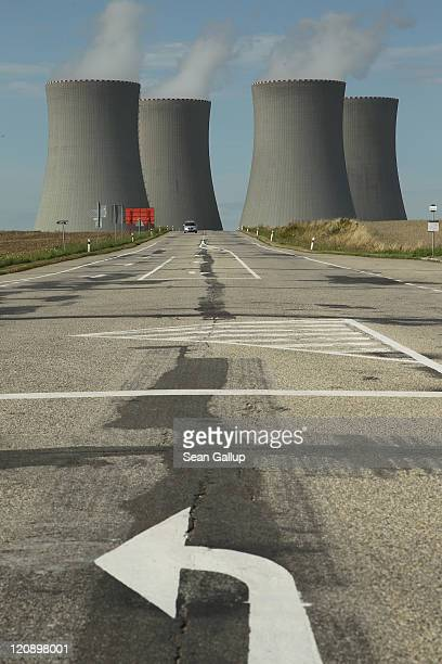 A traffic arrow points on a street that leads by the four cooling towers of the Temelin nuclear power plant on August 11 2011 near Temelin Czech...