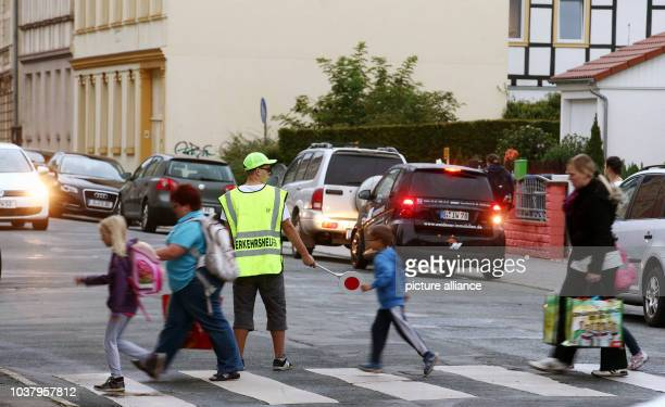 A traffic assistant for school children stands at a pedestrian crossing in front of the HansChristianAndersen primary school in Gera Germany 01...