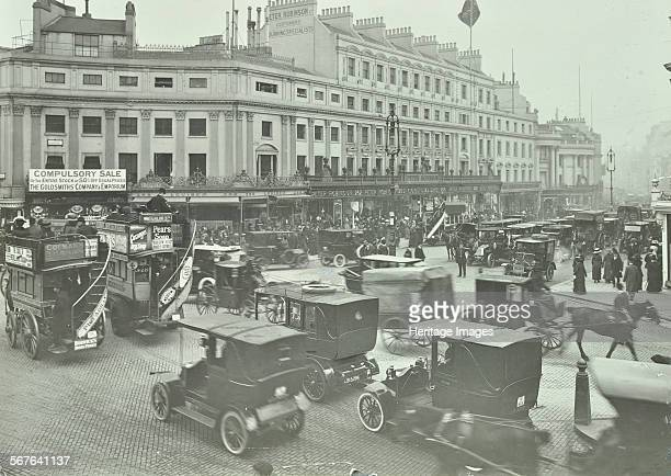 Traffic at Oxford Circus London 1910 Opentopped doubledecker horsedrawn buses motor cabs cars horsedrawn carriages and a protruding flag at the...