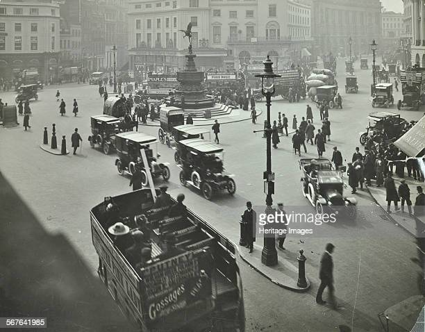 Traffic at Piccadilly Circus London 1912 Cars vans and an opentopped omnibus in the foreground pedestrians cross between the traffic with the statue...