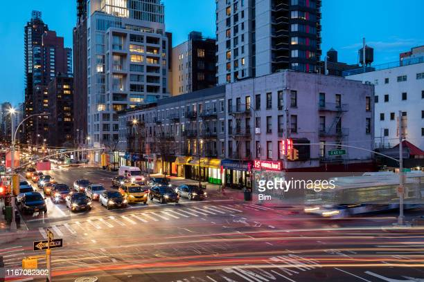 traffic at streets intersection at dusk in midtown manhattan, new york city - road junction stock pictures, royalty-free photos & images