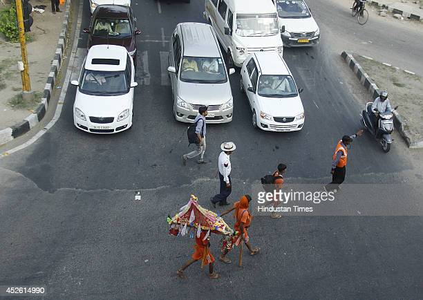 Traffic being stopped as Hindu pilgrims known as Kanwariyas crossing the road on July 24 2014 in Gurgaon India Kanwar Yatra is annual pilgrimage...