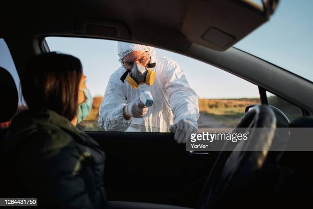traffic border control, medical worker with protective equipment measuring the temperature of a woman in car. - department of health and human services stock pictures, royalty-free photos & images