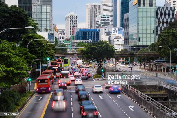 Traffic, captured with blurred motion, rushing in the street of Singapore downtown district in Singapore