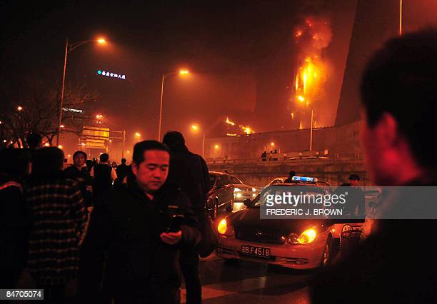 Traffic comes to a standstill as bystanders watch a spectacular fire engulf a building being constructed about 500 metres north of the CCTV tower one...