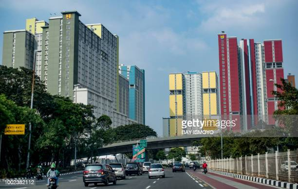 Traffic commutes next to the newly-completed athletes village in Kemayoran district, central Jakarta on July 20 ahead of the 2018 Asian Games which...