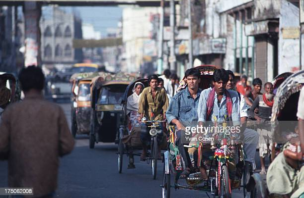 Traffic composed of rickshaws and three-wheeler taxis known as 'baby taxis' move along a street in the Bangladeshi capital. Rickshaws pulled by...