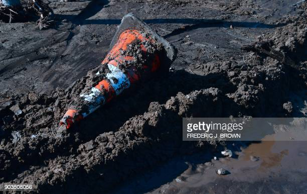 A traffic cone is seen in mud along La Tuna Canyon Road in Sun Valley neighborhood of Los Angeles California on January 10 2018 The death toll from...