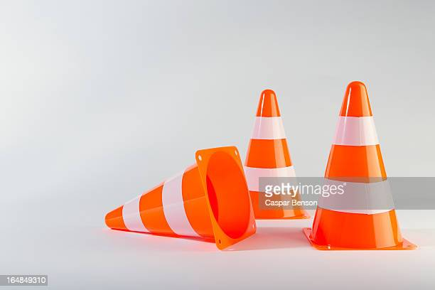 a traffic cone lying on its side next to two standing traffic cones - traffic cone stock pictures, royalty-free photos & images