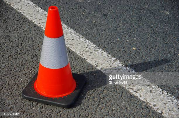 traffic cone next to the line marking on the shoulder of a road - traffic cone stock pictures, royalty-free photos & images