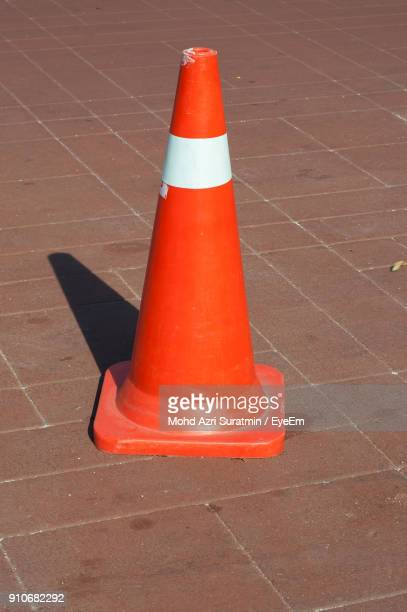 traffic cone on footpath during sunny day - traffic cone stock pictures, royalty-free photos & images