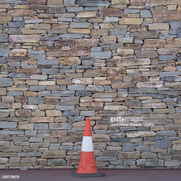 traffic cone on sidewalk against stone wall - javier alonso fotografías e imágenes de stock
