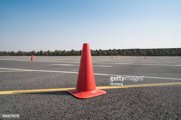 traffic cone,an image of cautions on asphalt road - cone shape stock photos and pictures