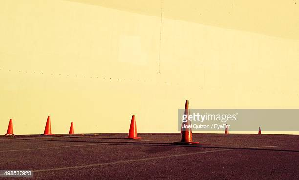 Traffic cones against white wall