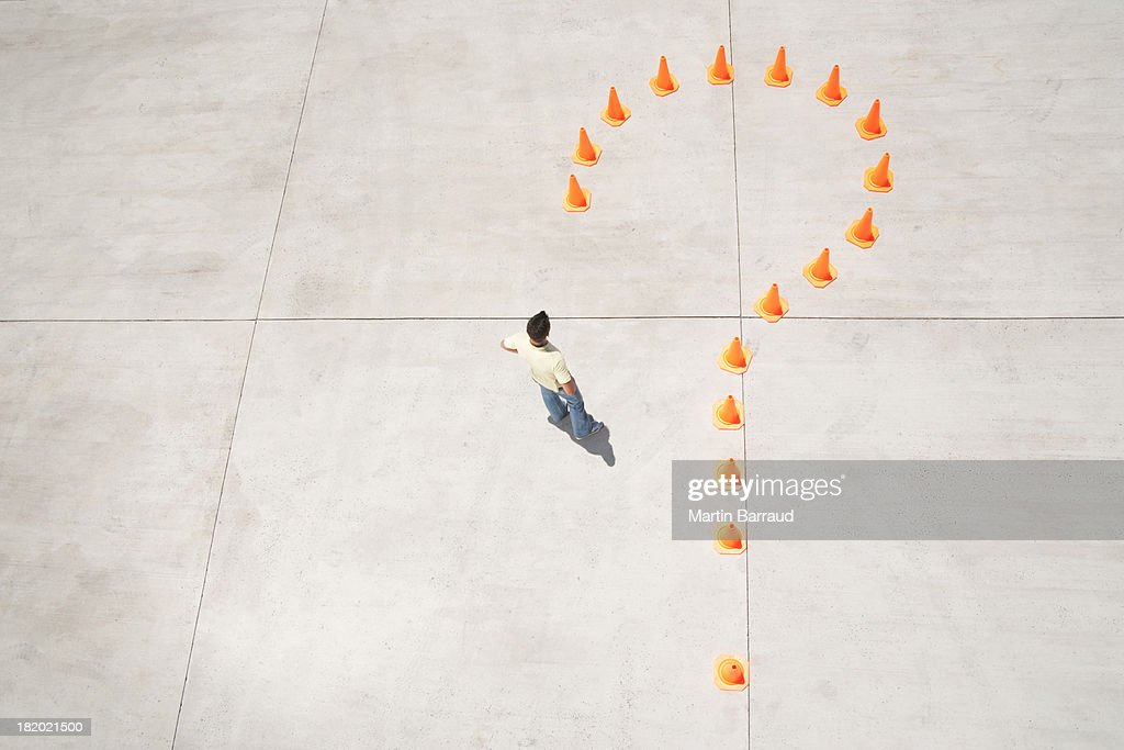 Traffic cones forming question mark with man inside : Stock Photo