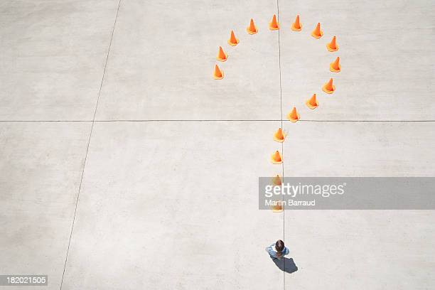 Traffic cones forming question mark with woman at point standing