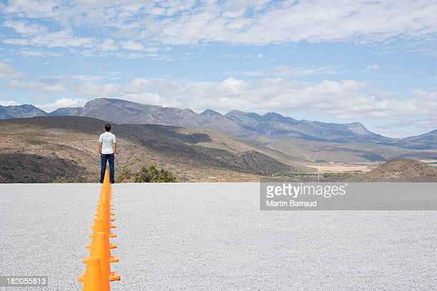 Traffic cones in line outdoors with man at end