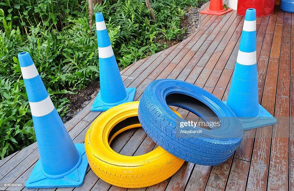 Conos de tráfico con pintura azul y amarillo Neumáticos : Foto de stock