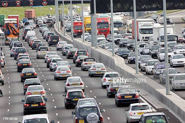 Traffic congestion of cars and lorries travelling in both directions on M25 motorway London United Kingdom