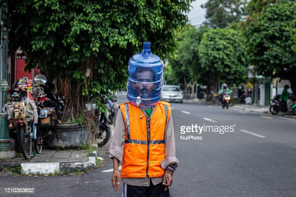 Traffic control volunteer wears a unique face shield from used water gallon in Yogyakarta, Indonesia on April 18 to prevent the spread of coronavirus...